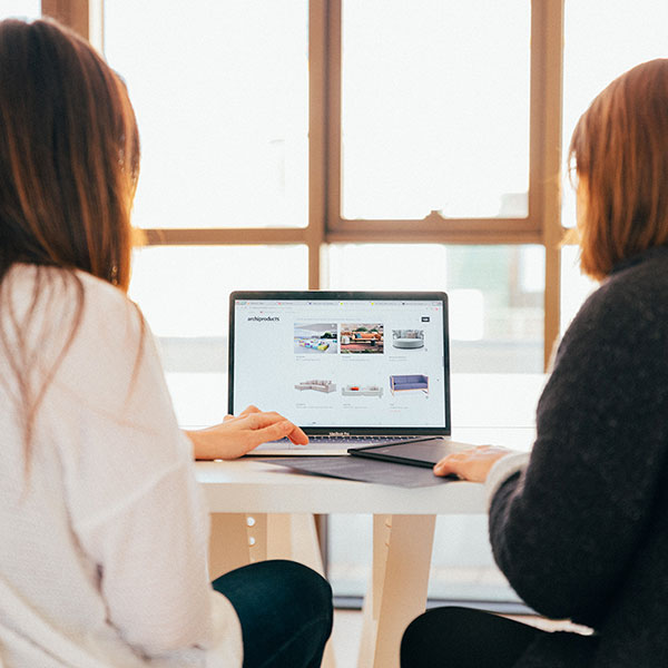An image of two people working at a single computer