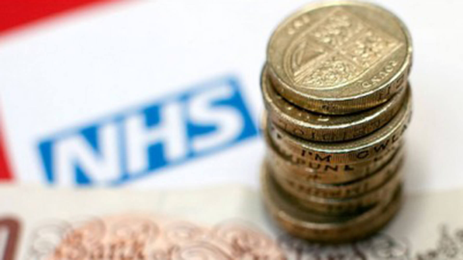 The NHS logo on a piece of paper with money on top of it