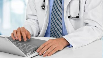 A doctor looking at analytics on a laptop