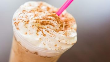 A Iced coffe with cream and a straw