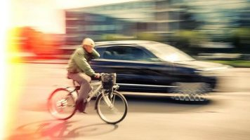 A cyclist riding past a moving car