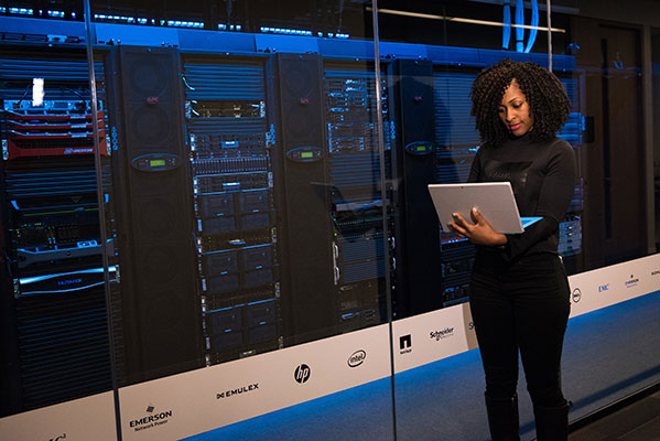 Image of a woman standing in a server room with a laptop